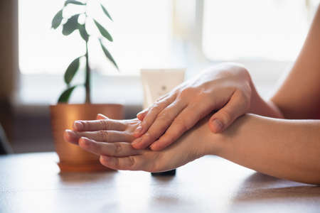 Woman is applying a moisturizer cream on her hands or anesthetic gel close up. Stock fotó