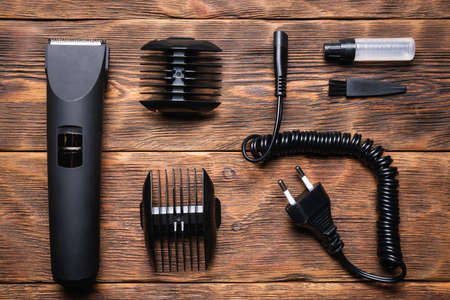 Hair clipper on the hairdresser work table flat lay background.