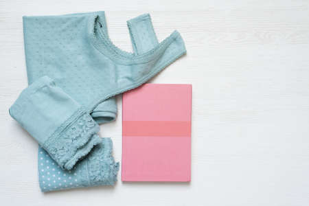 A women shirts, panties and notepad on the white table flat lay background with copy space.
