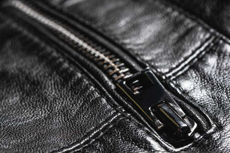 Zip clasp close up on the black leather clothes abstract background.