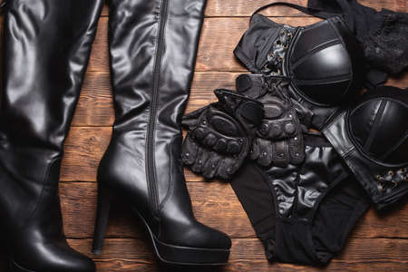 Various black leather clothes flat lay background. Bra, panties, high heels boots and stockings on the wooden table background.