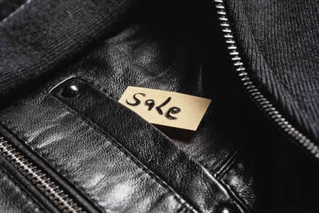 Sale tag label in the clothes pocket close up background. Discount concept.
