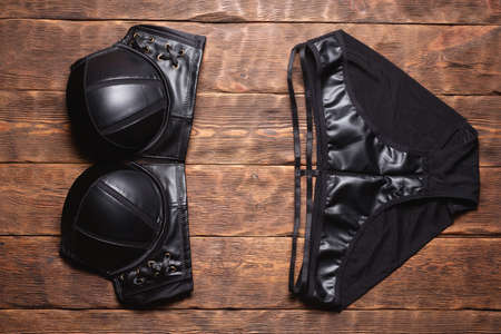 Black leather underwear on the wooden store counter flat lay background. Bra and panties top view.