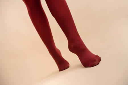 Female legs in the red stockings on a light background in the fitting room.