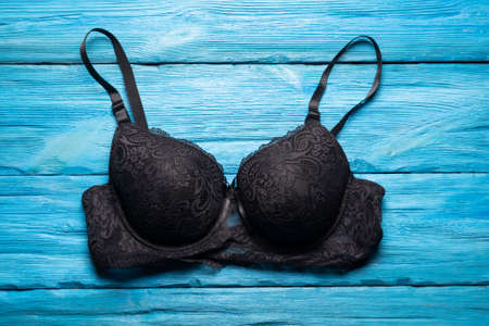 Black bra on the blue flat lay shop counter background. 写真素材
