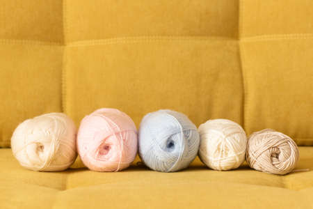 Balls of woolen threads on the sofa. Knitting background. 写真素材