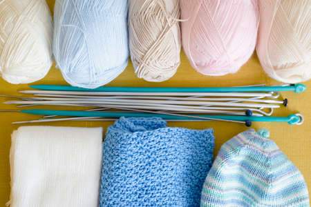 Balls of woolen threads, knitting needles and knitted clothes on the yellow sofa top view background.
