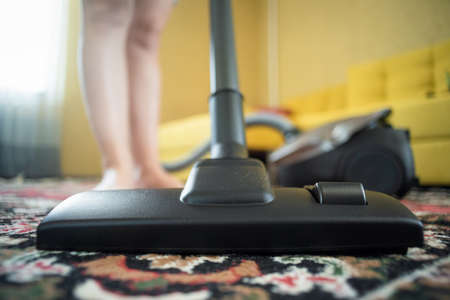 Woman is cleaning the carpet in the room with a vacuum cleaner. 写真素材