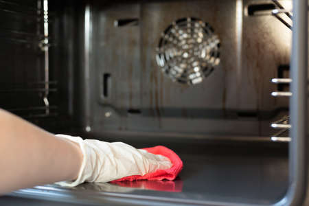 Woman is washing a kitchen gas stove by the rag with detergent close up. 写真素材
