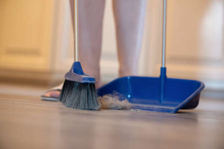 Broom brush and dustpan on the floor. Home cleaning.