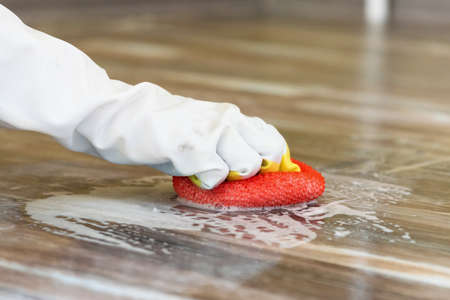 Woman hand is mopping a floor by the sponge and laundry soap.
