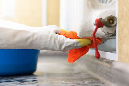 Woman is washing a home heating battery by the rag close up. 写真素材