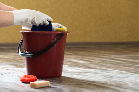 Bucket, sponge and laundry soap on the dirty floor background.