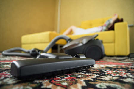 Overworked tired woman is lying on the sofa with a vacuum cleaner on the foreground.
