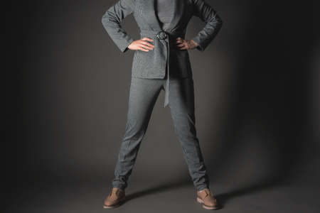 Confident business woman is standing with her arms on her belt on a gray background. 写真素材