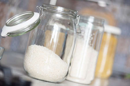 A white rice in the food container jar on the kitchen table background. 写真素材
