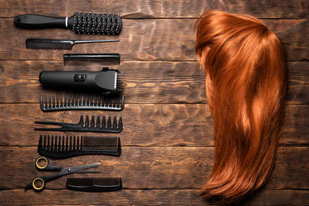 Hairdressing flat lay concept background. Hairdresser tools and female wig on the hairdresser table background.