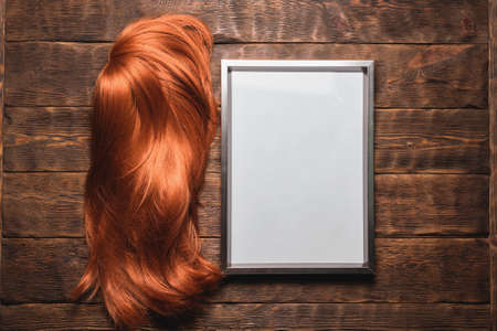 Hairdresser diploma certificate template. Empty picture frame and female long hair red wig on the brown table background. 写真素材