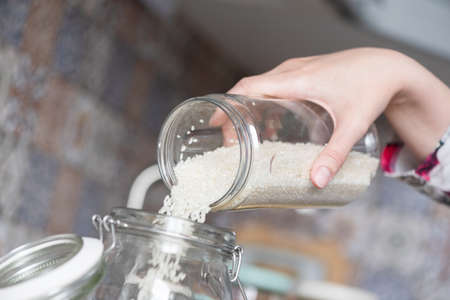 A woman is pouring the white rice from a food container into the jar close up.