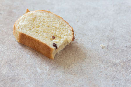 A slice of bread on the kitchen table background.