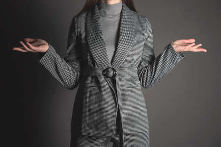 A woman in a gray suit is spreading her hands and shrugs her shoulders. Business mistake. 写真素材