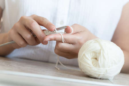 A woman is knitting with the knitting needle close up.