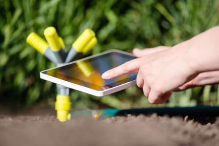 A gardener with a tablet using a smart garden application concept. Watering system. Electronic irrigation control.