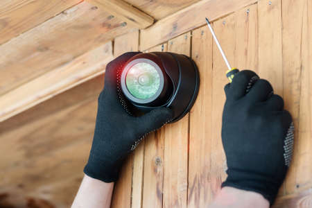 Worker installs a video surveillance camera on the wall of a country house concept. 写真素材