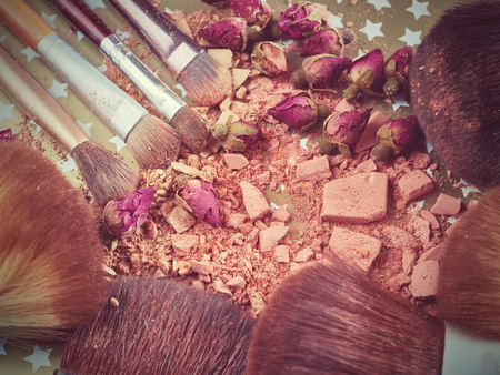 Close-up of crushed powder and blush beige color with makeup brush. Stock Photo