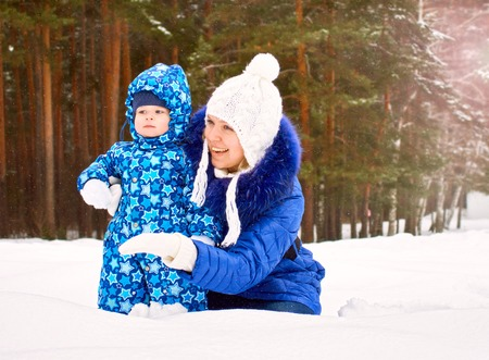 Happy and joyful mother and child on walk, play in the winter forest. Pine forest of Chelyabinsk region, Ural, Russia. Family portrait Stock Photo