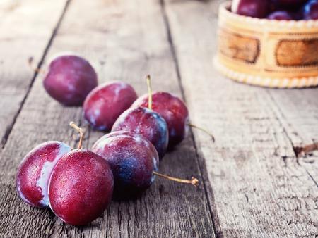 Fresh ripe plum prunes crop harvest, on wood background, organic, healthy food, rustic vintage retro style