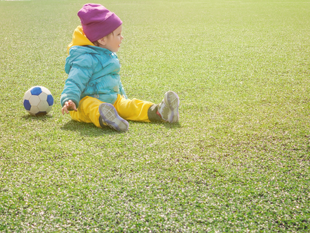 Little girl child on football field, in sportswear, training, plays with soccerball on artificial lawn