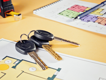 Linking new key on project plan of apartment house Concept new residence house warming Buying Selling Real Estate Stock Photo