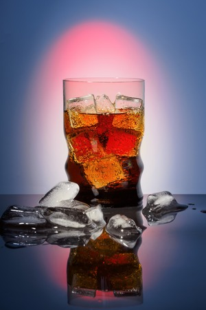 advertizing: Cola in drinking glass with ice sweet sparkling carbonated drink beverage fast food with big calorie Advertizing background with red light and vignetting on black table with reflection.