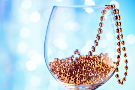 Festive card ornament golden decor in wine glass against sparkling bokeh of holiday party light. Christmas concept congratulation New Year.