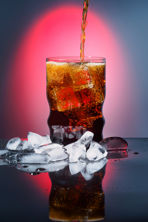advertizing: Cola in drinking glass with ice sweet sparkling carbonated drink beverage fast food with big calorie Advertizing background with red light and vignetting on black table with reflection