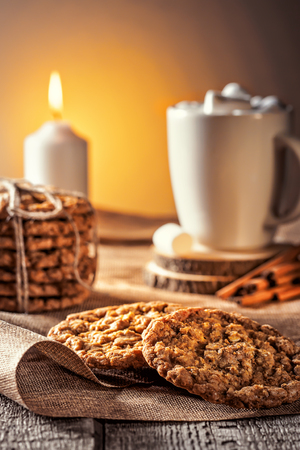 Winter autumn still life  homemade recipe honey ginger oatmeal cookie and bagel, cocoa cup coffee with marshmallow on wooden table kitchen Jute, burlap Rustic rural scene closeup with copyspase