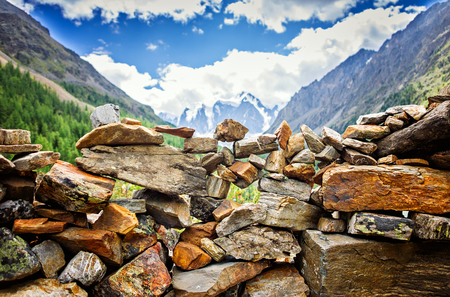 Picturesque landscape, handmade wall of stone on river bank dawn sunrise backpacking against background of high mountain, wild nature, ecological tourism, Mountain Altai Russia