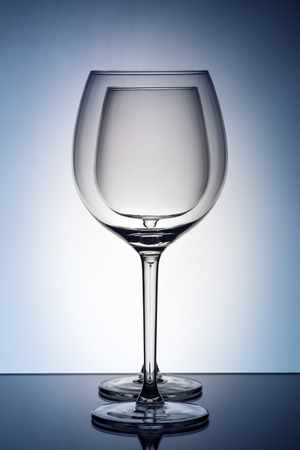 Two empty wineglass for red wine on diffusion lit background in abstract   composition with reflection, advertizing shot for restaurant, winemaking