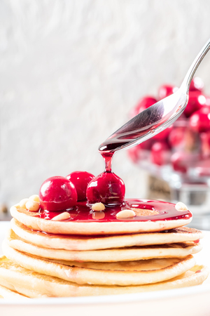 Pancakes homemade cake in stack decorated with berries frozen cherry and pine nut on white plate Sprinkling with cherry syrup 스톡 콘텐츠