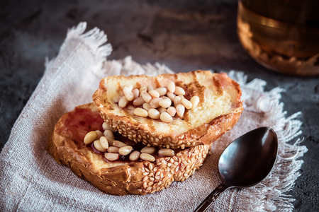 Toasts of bread with sesame seeds homemade cake in stack decorated with pine nut and spoon on linen cotton napkin low key dark toned concept healthy breakfast on gray stone table background. Stock Photo