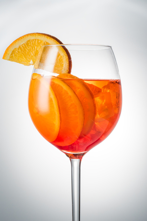Trendy popular Italian drink Summer refreshing faintly alcoholic cocktail Aperol spritz in a glass glass with ice decorated with orange slices on white gray Light diffusion gradient background Promotional advertising shot. Stock Photo