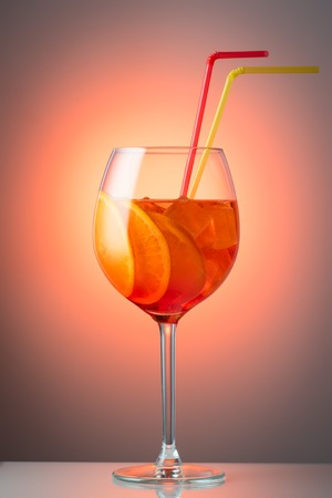 Trendy popular Italian drink Summer refreshing faintly alcoholic cocktail Aperol spritz in a glass with ice decorated with orange slices on a color red yellow Light diffusion gradient background Promotional advertising shot. Stock Photo