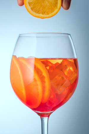 Trendy popular Italian drink Summer refreshing faintly alcoholic cocktail Aperol spritz in a glass glass with ice decorated with orange slices on  color  blue Light diffusion gradient background Promotional advertising shot Imitation of fresh orange juice with drop.