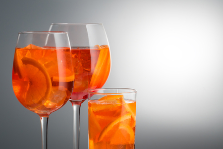 Trendy popular Italian drink Summer refreshing faintly alcoholic cocktail Aperol spritz in a glass glass with ice decorated with orange slices on white gray Light diffusion gradient background Promotional advertising shot set of three different glasses. Stock Photo