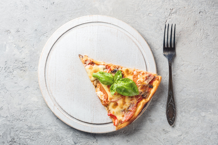 Two piece of Italian pizza with tomatoes mushrooms bacon and cheese and basil leaves on wooden white round board cutting kitchen and plug fork on gray stone background Food macro  close-up and copy space.