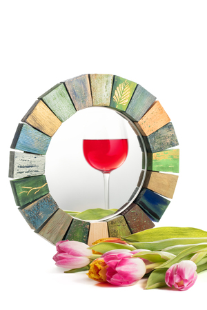 Handmade mirror in a wooden toned frame texture cracked paint rustic style with a reflection of a glass of red wine and a bouquet of tulips on a white background isolated concept idea reality and anticipation window. Stock Photo