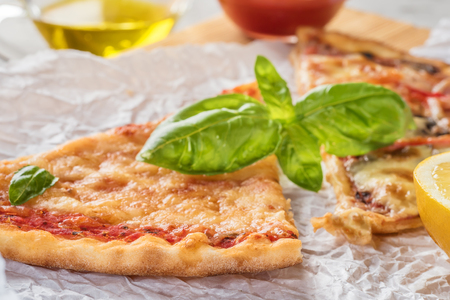 Two pieces of pizza with mushrooms and cheese and also with lemon slices and basil leaves on a wooden board covered with baking paper, served with tomato sauce and olive oil on a gray concrete stone background Stock Photo