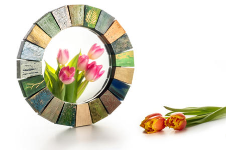 Interior design mirror handmade in wooden frame with painted cracks aged paints for makeup of women on a white background isolated and a bouquet of spring tulips on a table and in reflection of glass with copy space and close-up of a macro.
