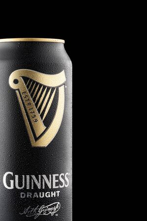 CHELYABINSK, RUSSIA - April 11,2018 Close Up of Aluminum can of Guinness draught beer with drops advertising shot on black background with realistic reflection Guinness beer one of the most successful beer brands worldwide popular Irish dry stout original Editorial